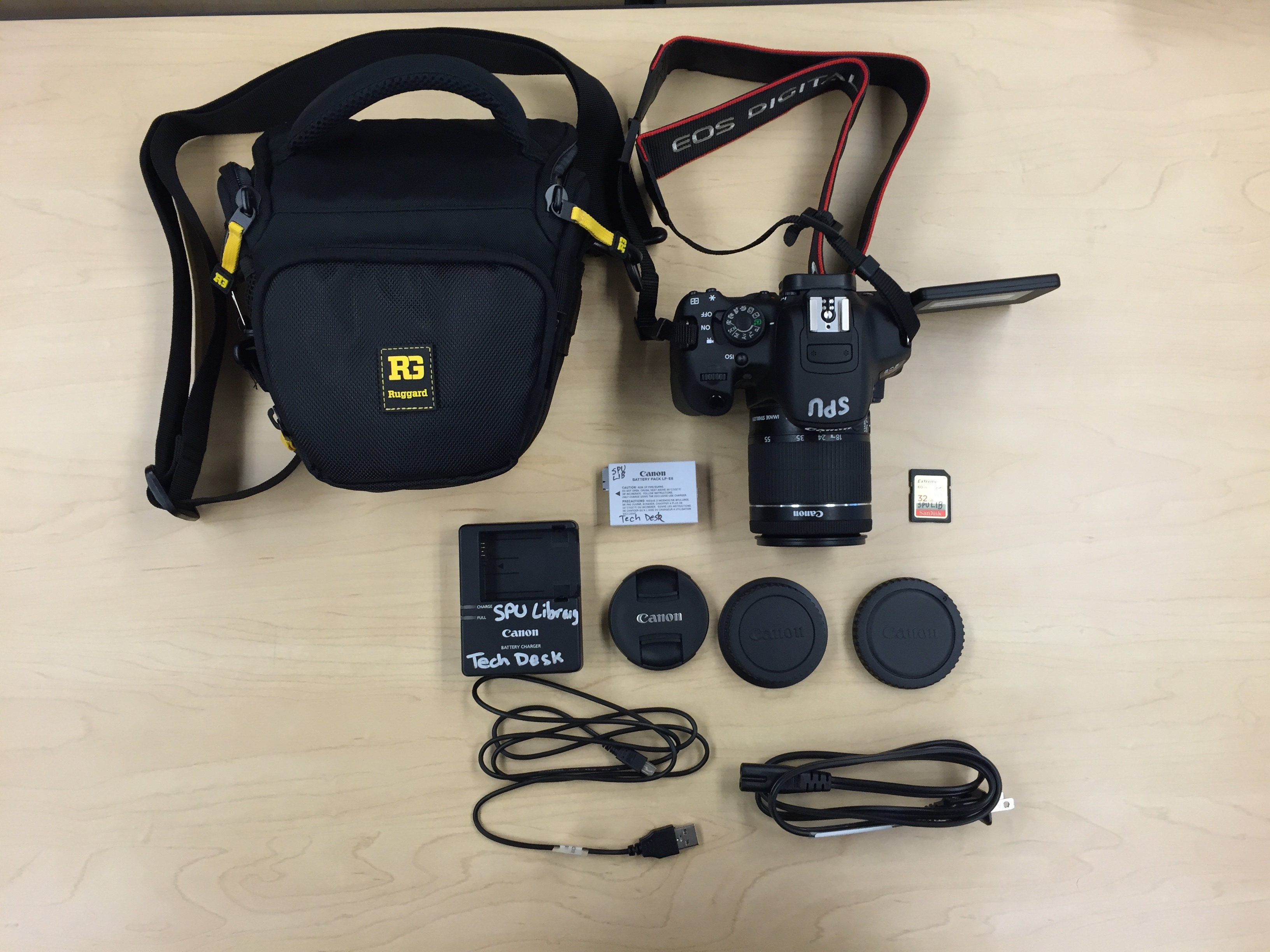Canon EOS Rebel T5i Camera with shoulder strap, lens, lens cap, 2 lens storage caps, battery charger, battery power cable, battery pack, USB cable, Hunter case, SD card